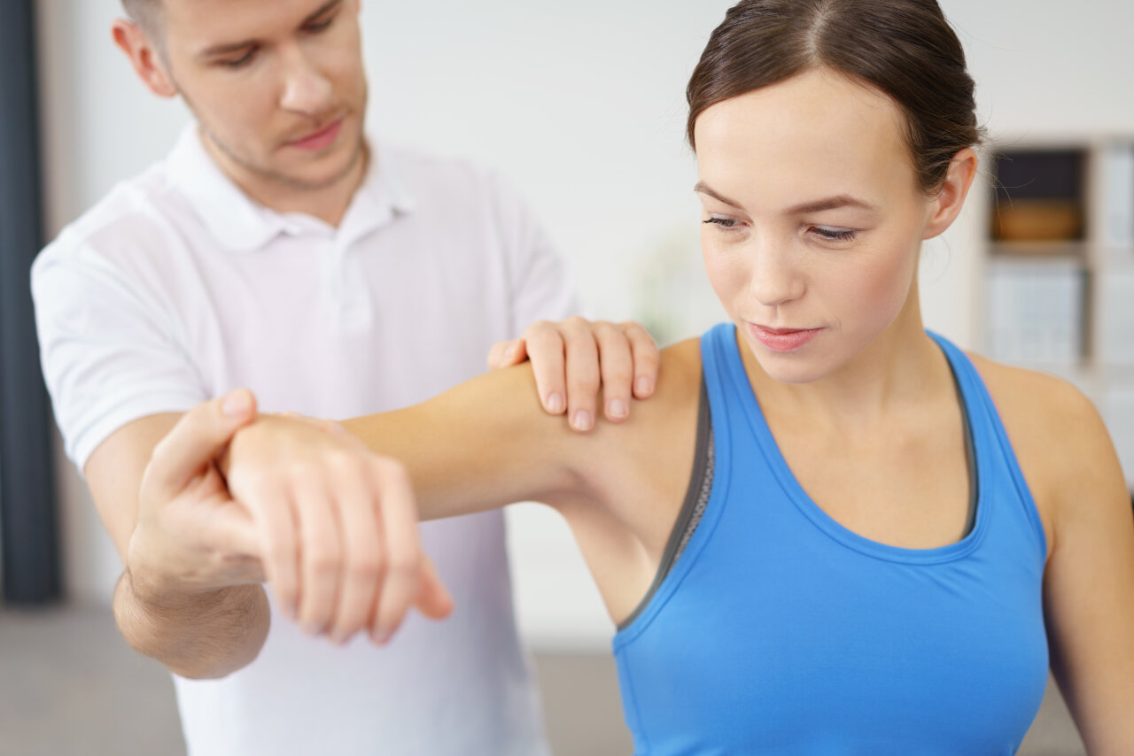 Osteopath assessing a female patients' shoulder