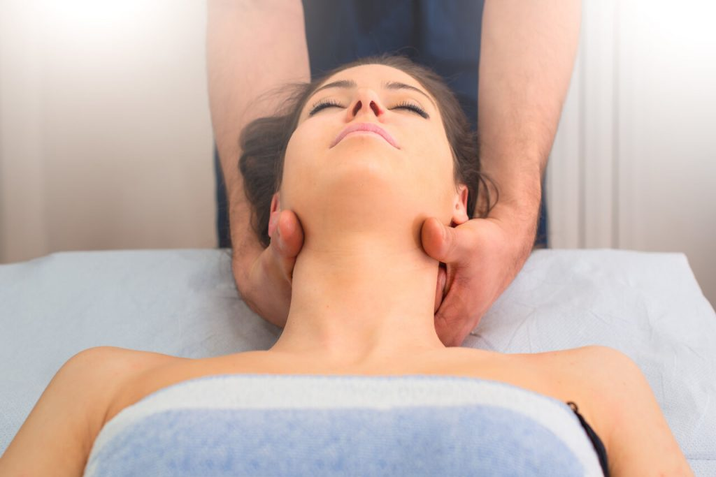 Therapist massaging the neck of woman In the by a professional in studio