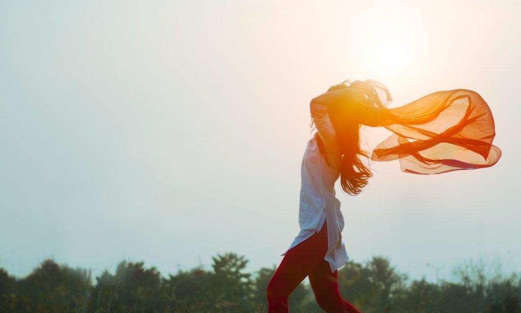 Side view of woman walking in a sunny light breeze holding an orange scarf joyfully