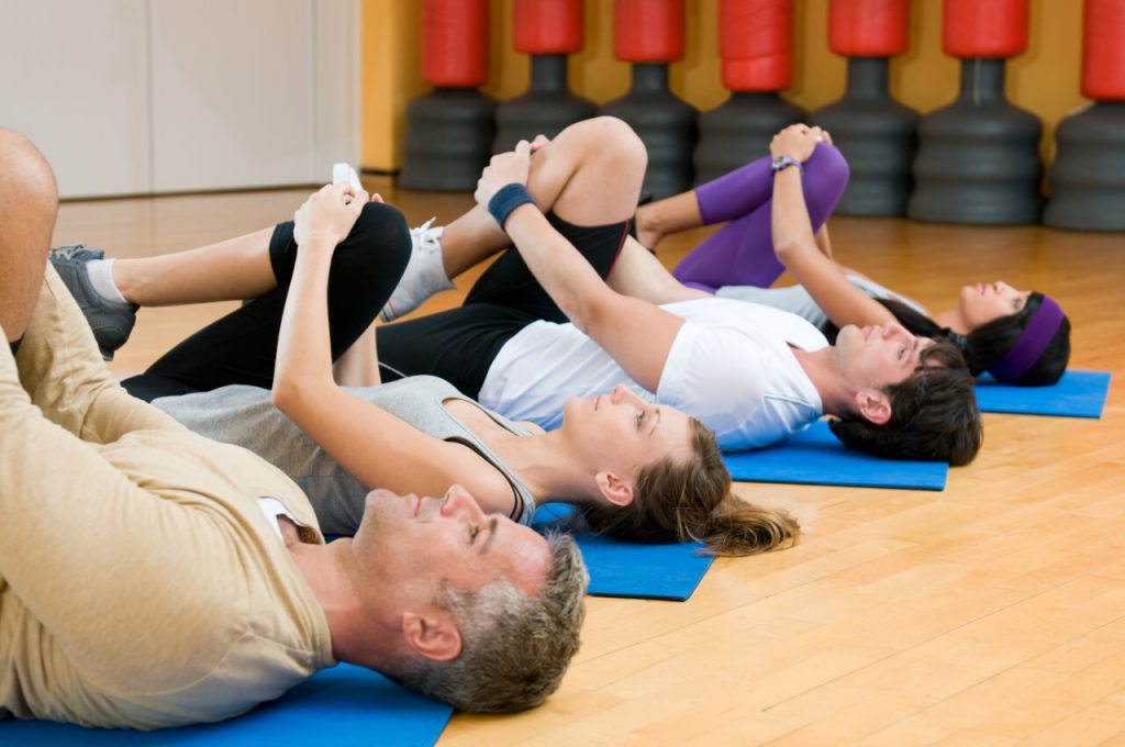 four people lying on their backs on pilates mats doing exercise