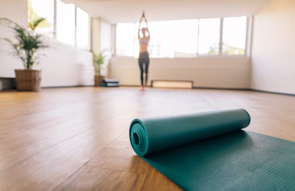 Exercise mat on floor with woman practising yoga in background. Close up of yoga mat in fitness center and blurred female at the back exercising.