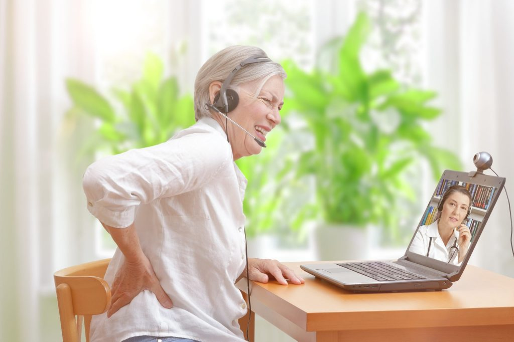 Senior woman with low back pain in her living room in front of a laptop making notes during a video call with her female doctor
